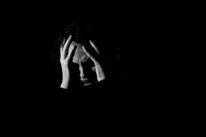 Grayscale photo of person covering face